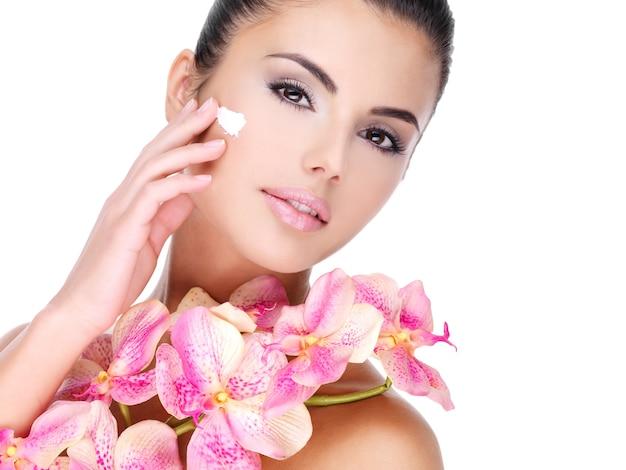 Hermosa mujer aplicando crema cosmética en la cara con flores rosadas en el cuerpo - aislado en blanco