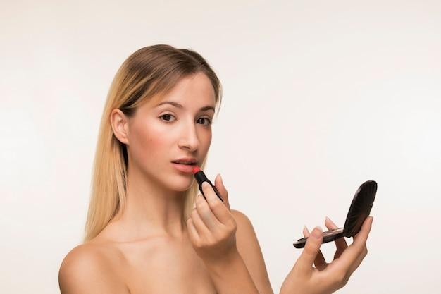 Hermosa mujer aplicando lápiz labial