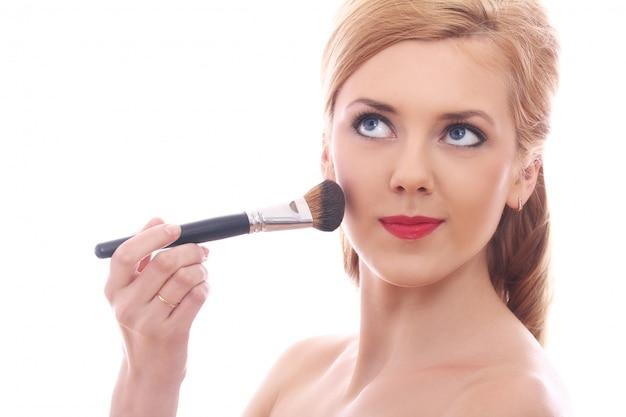 Hermosa mujer aplicando maquillaje con pincel