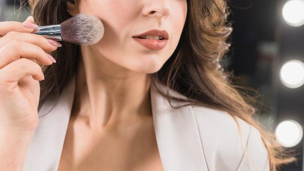 Hermosa mujer aplicando polvo con pincel de maquillaje