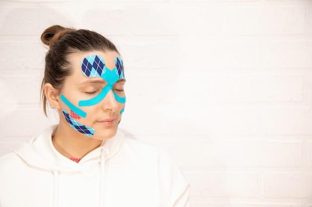 Hermosa mujer aplicando el procedimiento de tratamiento de levantamiento de cinta en la cara proceso de envejecimiento