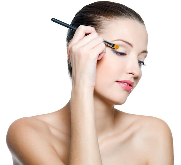 Hermosa mujer aplicando sombra de ojos con pincel aislado en blanco