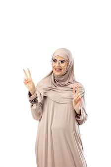 Hermosa mujer árabe posando en elegante hijab aislado en concepto de moda