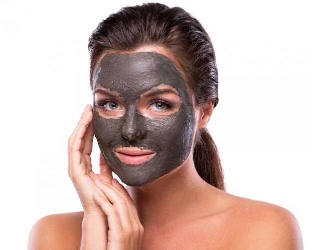 Hermosa mujer con una arcilla o una máscara de barro en la cara