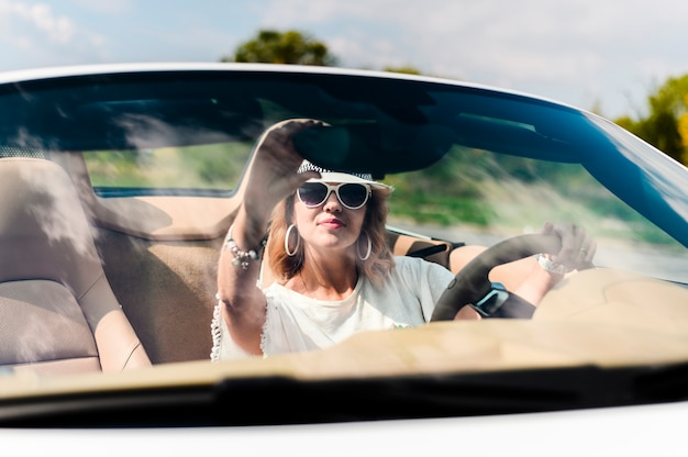 Hermosa mujer arreglando espejo de coche