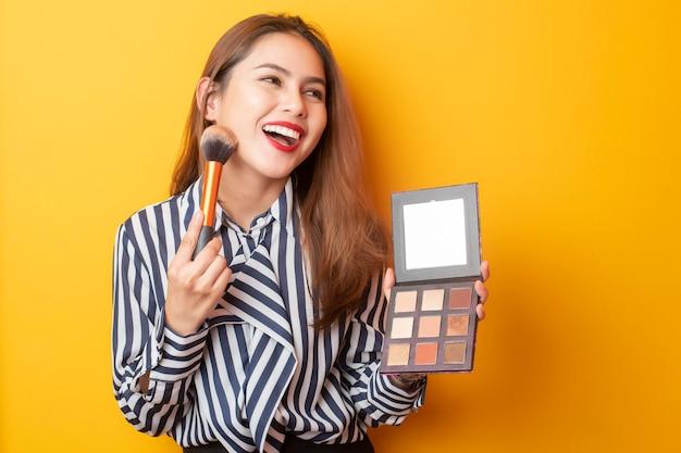 Hermosa mujer artista de maquillaje es feliz sobre fondo amarillo