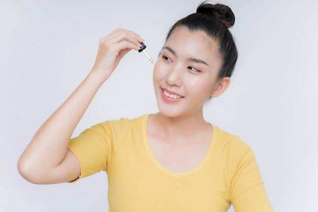 Hermosa mujer asiática aplicando suero hidratante anti envejecimiento en su rostro