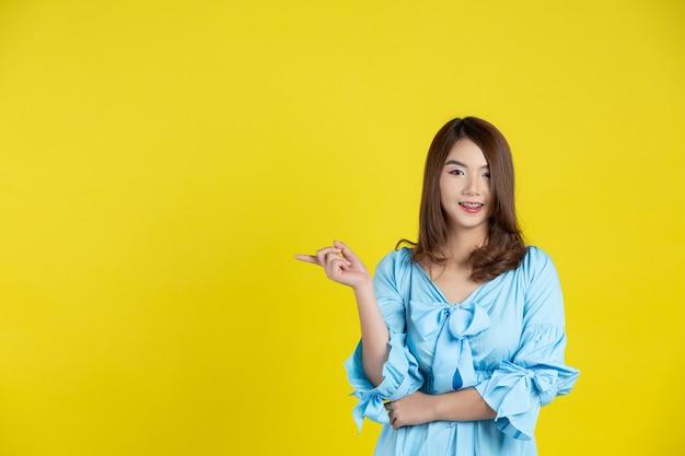 Hermosa mujer asiática apuntando con la mano al espacio vacío a un lado en la pared amarilla