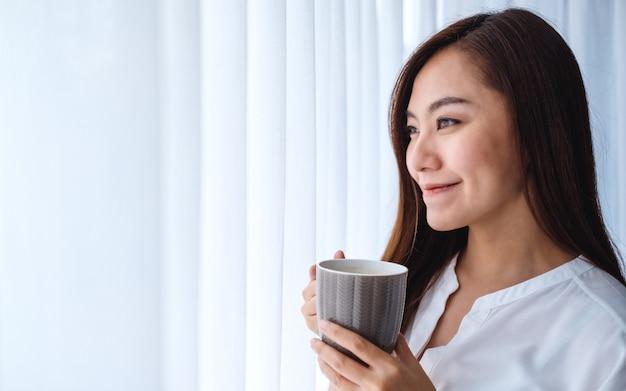 Una hermosa mujer asiática bebiendo café caliente mientras mira por la ventana por la mañana