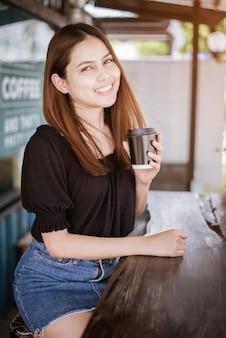 Hermosa mujer asiática está bebiendo café