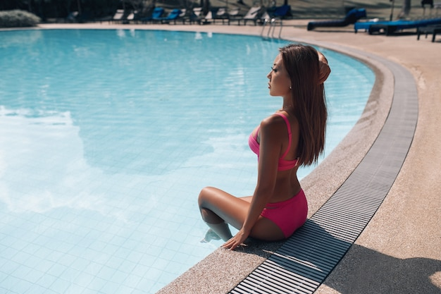 Hermosa mujer asiática en bikini rosa sentada junto a la piscina cristalina