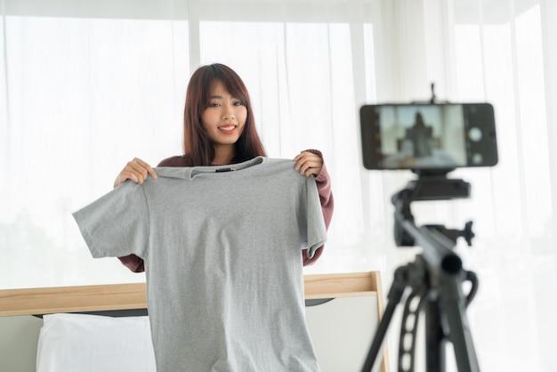 Hermosa mujer asiática blogger mostrando ropa en cámara para grabar video vlog