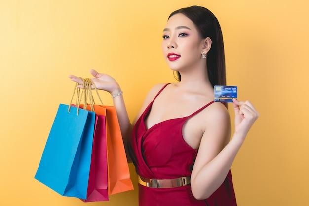 Hermosa mujer asiática con bolsa y tarjeta de crédito en mano