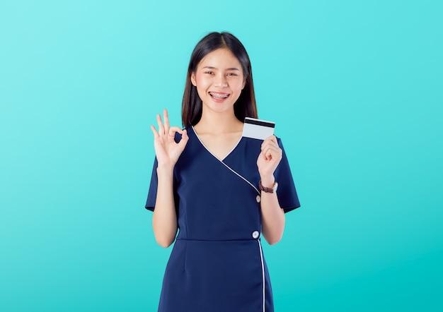 Hermosa mujer asiática buena piel, muestra signo bien con vestido y con pago con tarjeta de crédito sobre fondo azul.
