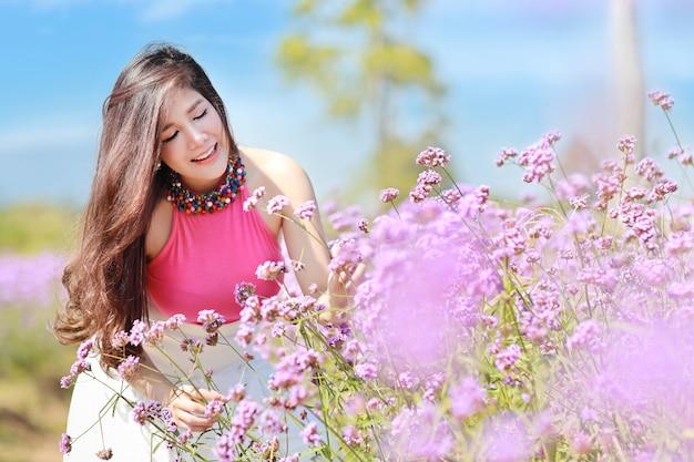 Hermosa mujer asiática, cabello largo en lindo vestido en verbena presentada en invierno con cielo azul.