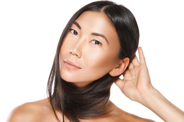 Hermosa mujer asiática con un cabello negro sano en la pared blanca