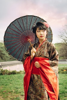 Hermosa mujer asiática caminando en el jardín