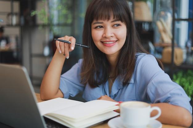Hermosa mujer asiática en camisa azul usando laptop y tomando café