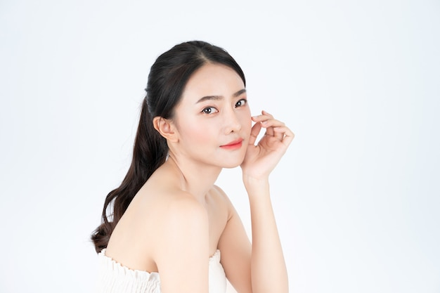 Hermosa mujer asiática en camiseta blanca muestra una piel brillante y saludable.