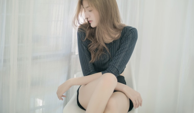 Hermosa mujer asiática cierra los ojos y se sienta en una silla en su habitación