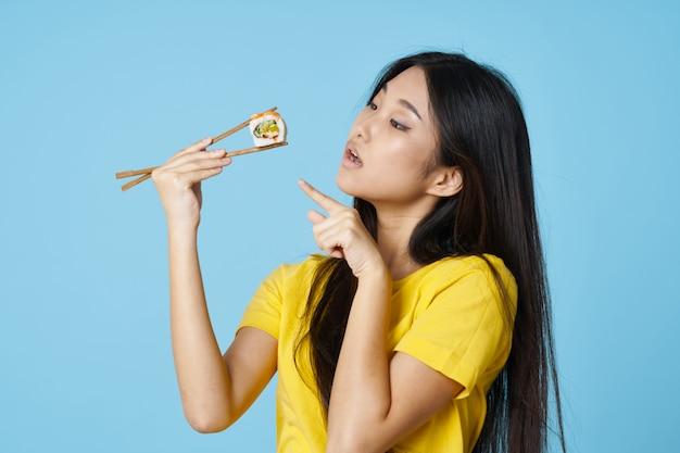 Hermosa mujer asiática comiendo sushi con palillos