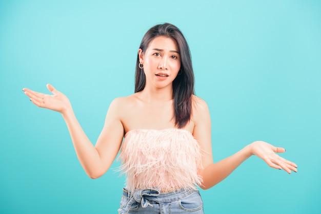 Hermosa mujer asiática confundida, tirando las manos a un lado