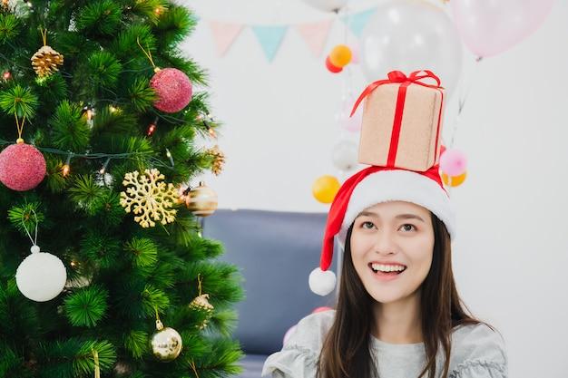Hermosa mujer asiática está decorando el árbol de navidad en la sala blanca con una caja de regalo colocada en la cabeza. cara sonriente y feliz de celebrar festivel vacaciones de año nuevo.