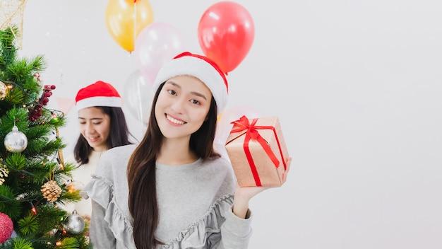 Hermosa mujer asiática está decorando el árbol de navidad en la sala blanca con la mano que sostiene la caja de regalo. cara sonriente y feliz de celebrar festivel vacaciones de año nuevo.
