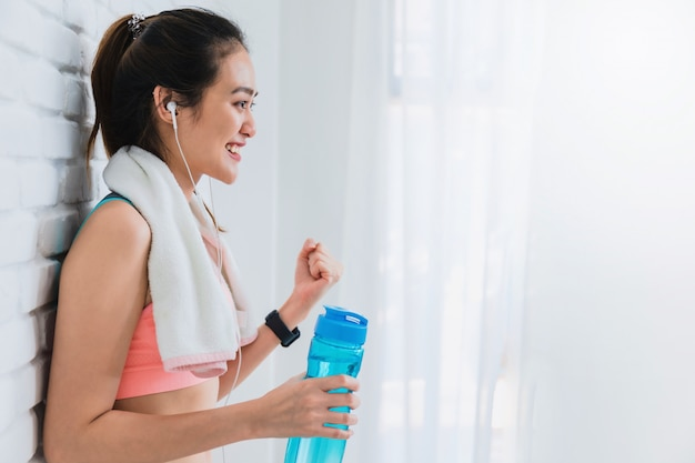 Hermosa mujer asiática descansando y sosteniendo la botella de agua después de jugar yoga y ejercicio sobre fondo de pared de ladrillo blanco.