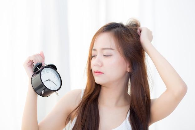 Hermosa mujer asiática despierta en la mañana molesto despertador.