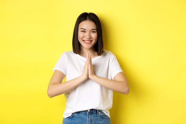 Hermosa mujer asiática dice gracias, tomados de la mano en namaste, gesto de oración y sonriendo, siendo agradecido, de pie sobre fondo amarillo.