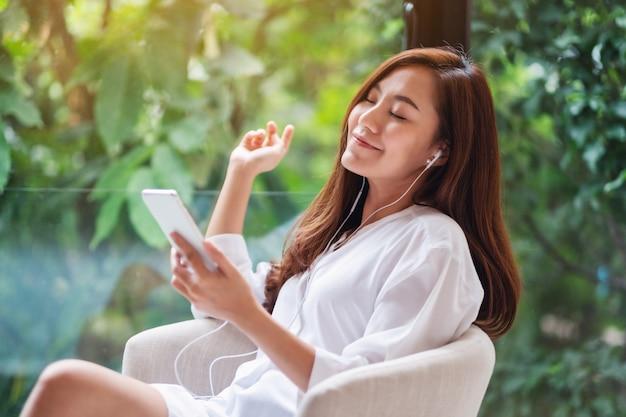 Una hermosa mujer asiática disfruta escuchando música con teléfono y auriculares en casa, conceptos de naturaleza verde, felicidad y relajación