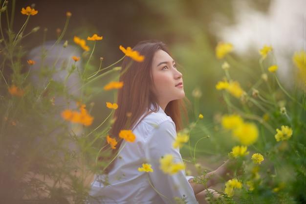 Hermosa mujer asiática disfruta con jardín de flores