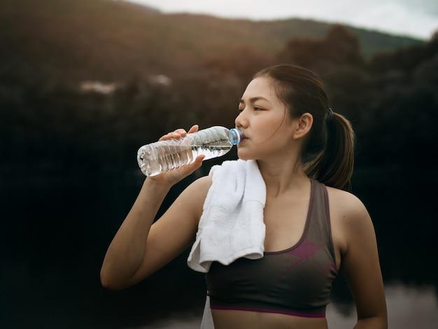 Hermosa mujer asiática ejercicios afuera y bebe agua