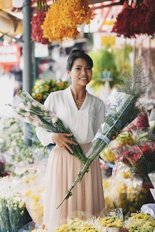 Hermosa mujer asiática elegir ramos de flores en la tienda de flores