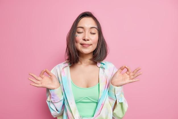 Hermosa mujer asiática se encuentra en pose de nirvana zen mantiene los ojos cerrados prácticas de yoga tiene pensamientos positivos respira calma y relajado disfruta de un ambiente pacífico usa poses de camisa colorida en interiores