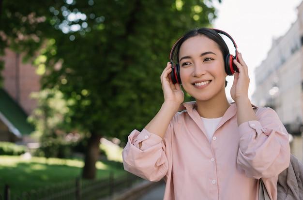 Hermosa mujer asiática escuchando música al aire libre