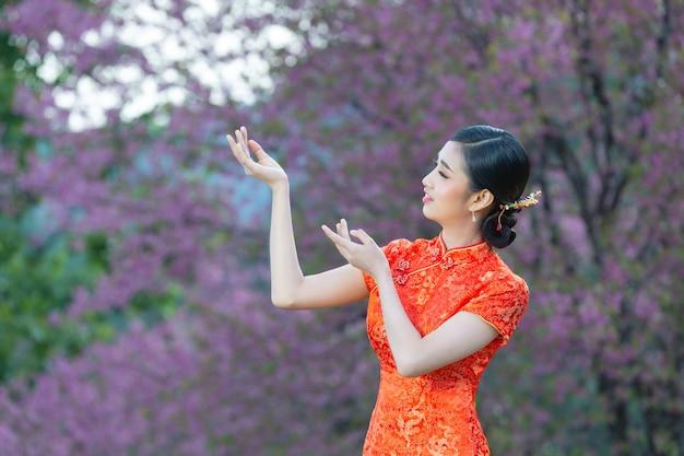 Hermosa mujer asiática feliz sonríe y te muestra algo en el año nuevo chino sobre fondo rosa.