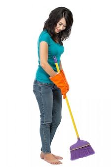 Hermosa mujer asiática con guantes, barriendo el piso con una escoba