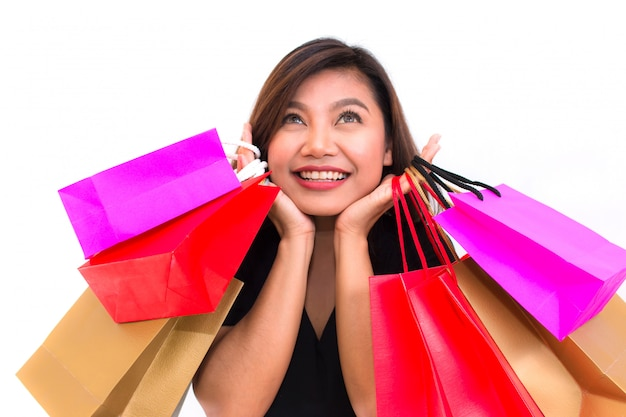 Hermosa mujer asiática joven con colorido llevar bolsas de compras en sus manos sonrisa y happi
