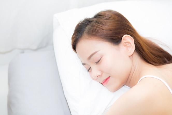 Hermosa mujer asiática joven durmiendo en la cama