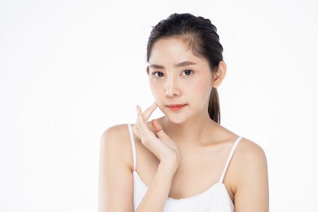Hermosa mujer asiática joven con piel blanca limpia y fresca tocando su propio rostro suavemente en pose de belleza.