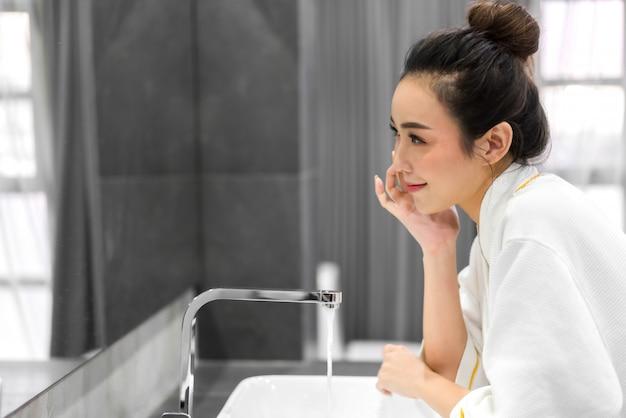 Hermosa mujer asiática joven que se lava la cara limpia con agua y sonriendo frente al espejo en el baño. belleza y spa. piel fresca perfecta