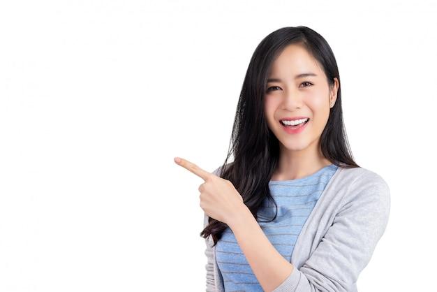 Hermosa mujer asiática joven que señala la mano al espacio vacío a un lado