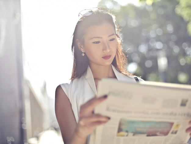 Hermosa mujer asiática leyendo un periódico