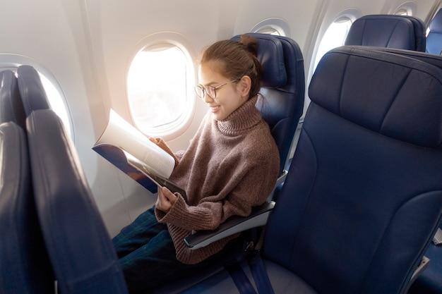 Hermosa mujer asiática está leyendo una revista en avión