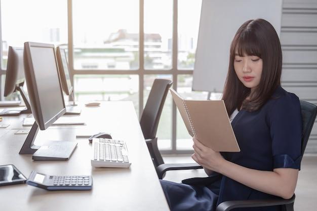 Una hermosa mujer asiática lleva un traje azul oscuro sentada en un escritorio en una oficina moderna y disfruta de su trabajo.