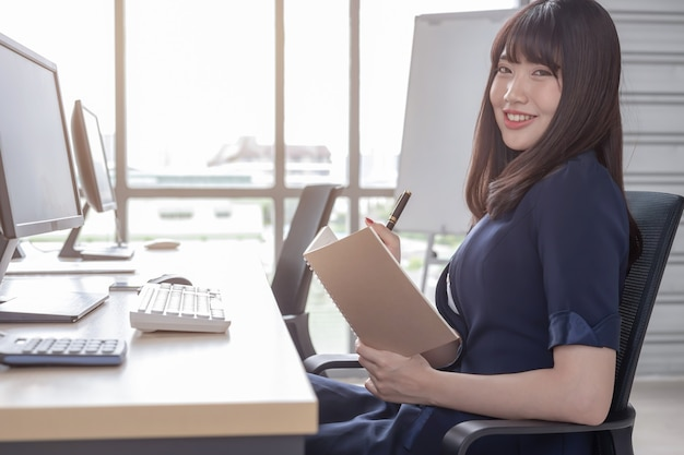 Una hermosa mujer asiática lleva un traje azul oscuro sentada en un escritorio en una oficina moderna y está feliz de trabajar y tiene un gran fondo de ventana de vidrio.