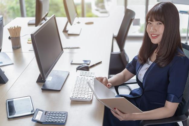 Una hermosa mujer asiática lleva un traje azul oscuro sentada en un escritorio en una oficina moderna y está feliz de trabajar y tiene una gran ventana de vidrio.