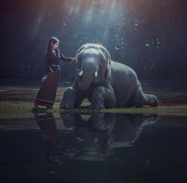 Hermosa mujer asiática lleva un vestido tailandés con su elefante, surin, campo de tailandia